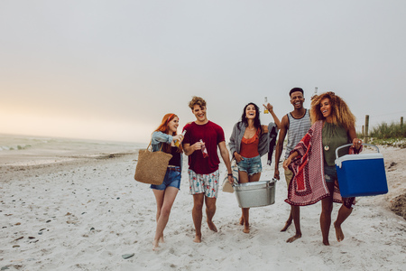 Group of young people walking on the beach carrying a cooler box and beverage tub. Young men and woman on sea shore. Stockfoto