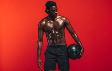 Shirtless man standing with medicine ball against red background. African american guy with muscular body holding a fitness ball and looking away. Banco de Imagens