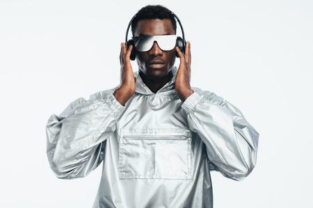 Apuesto joven afroamericano escuchando música con auriculares, gafas de sol espejadas y sudadera plateada. Hombre vestido como un robot sobre fondo aislado.