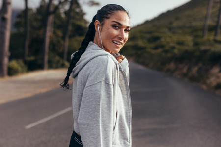 Rear view of young woman walking on empty road and looking over her shoulder. Sporty woman on country road with earphones on.