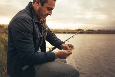 Side view of a man fishing near a lake in his leisure time.