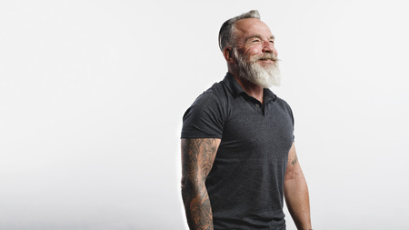 Happy senior man with tattoo on arms standing against white background. Portrait of old muscular male with a white beard looking away. Banco de Imagens