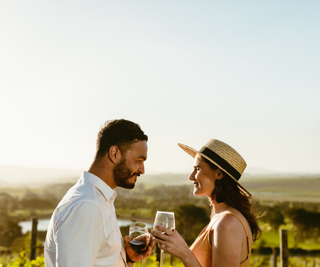 Happy couple looking at each other holding glass of red wine in a wine farm.