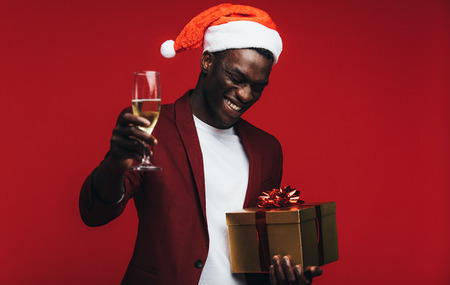 African man wearing santa hat with champagne and gift box against red