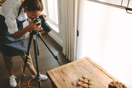 Female chef taking pictures of dessert on table with dslr camera mounted on tripod. Female taking pictures of sweet food for her blog. Imagens
