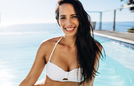 Attractive young woman in bikini sitting by the pool and smiling. Beautiful female enjoying a summer day at the poolside.