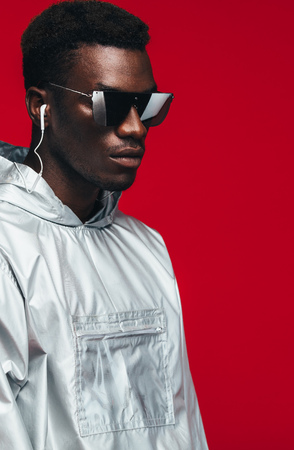 Trendy fashion portrait of man wearing silver outfit and stylish sunglasses.