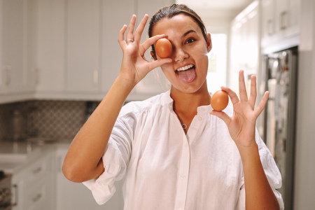 Funny woman with brown eggs sticking out her tongue in kitchen. Pastry chef having fun in the kitchen. Stock Photo