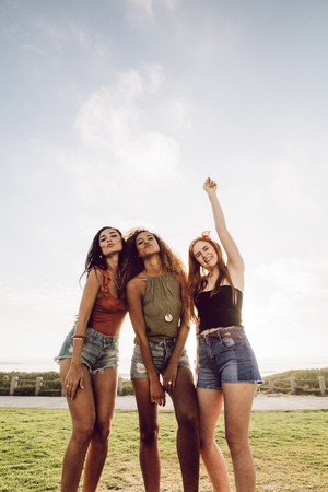 Excited young women standing outdoors with puckered lips and hand raised. Carefree girls in casuals posing outdoors for a picture. Imagens