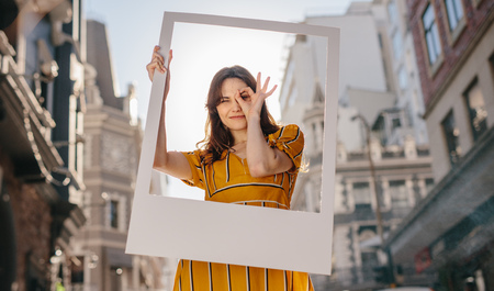 Pretty young woman standing outdoors holding a large empty frame. Woman looking through hole made of fingers while standing outdoors.