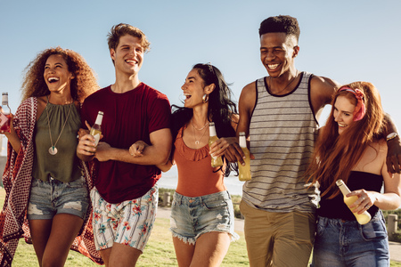 Group of friends walking together with locking arms. Young men and women with beers walking together and having fun. Imagens