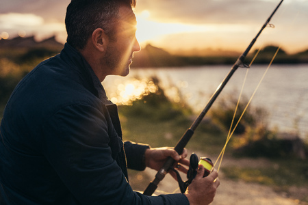 Close up of a man sitting near a lake holding a fishing rod. Side view close up of a man fishing near a lake with sun rising