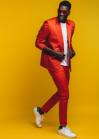 Full length of stylish young african man in orange outfit over yellow