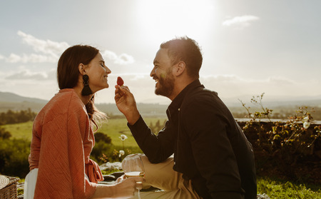 Happy couple on a date sitting in wine farm talking and having fun. Stock Photo
