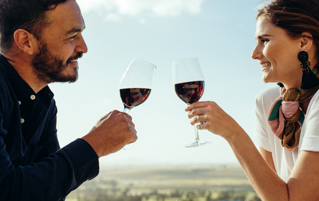 Cropped shot of a happy couple sitting together with glass of wine.