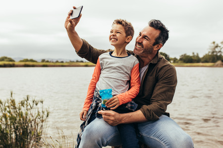 Man taking a selfie with his son sitting near a lake. Stock Photo