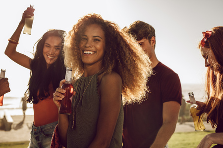 Cheerful young woman holding beer dancing with her friends outdoors. Imagens