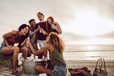 Glimlachende jonge vrouw met bierfles en vrienden staan op het strand.