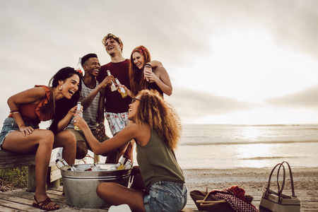 Smiling young woman with beer bottle and friends standing by on the beach. Banco de Imagens
