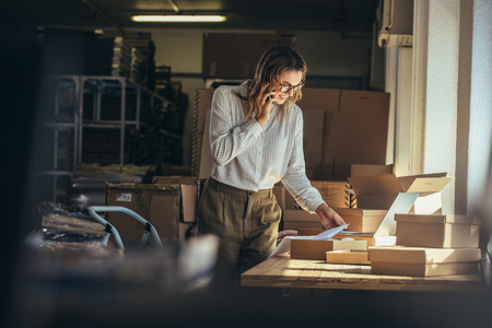 Woman online seller confirming orders from customer on the phone. E-commerce business owner looking at the papers and talking on phone in store warehouse.