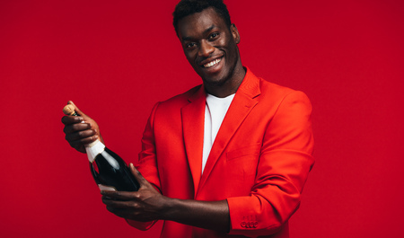 Handsome young african man about to open a champagne bottle against red Stock Photo