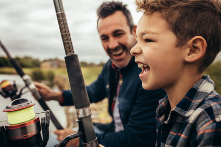 Close up of a smiling man fishing along with his son in a lake. Stock Photo