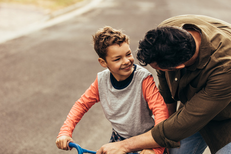 Father instructing his son on riding a  bicycle. Stock Photo