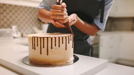 Cerca de las manos de una cocinera con bolsa de confitería exprimiendo chocolate líquido en la torta.