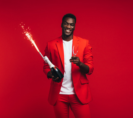 Handsome young african man with champagne bottle, glass and firework in hand.