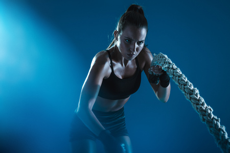 Athlete moving the ropes in wave motion as part of fat burning workout. Sportswoman exercising with battling ropes on blue background.