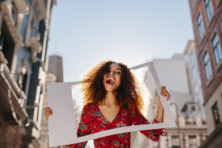 Excited young woman with empty photo frame. Women traveler standing outdoors in the city.
