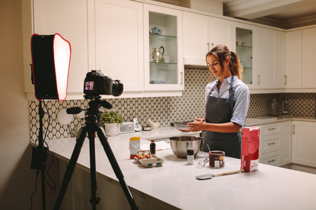Young woman wearing apron filming herself preparing cake in the kitchen.