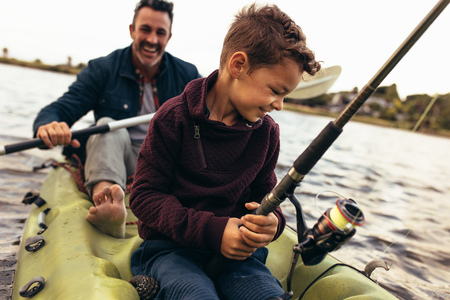 Close up of a kid sitting in a kayak fishing with his dad Imagens