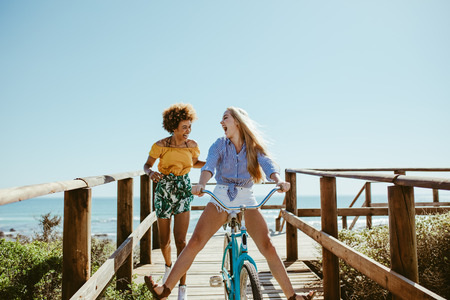 Young woman riding bike on boardwalk with friend running by. Multi-ethnic girls having fun with a bike at the seaside boardwalk. Stock Photo