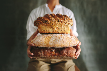 Close up of female chef holding different types of bread in hand. Imagens