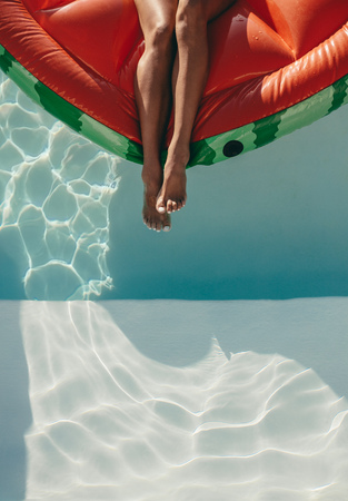 Cropped shot of woman legs on a floating mattress in swimming pool.