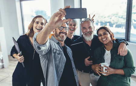 Cheerful multi-ethnic people in the office smiling and taking the selfie. Businessman taking selfie with his colleagues in office.