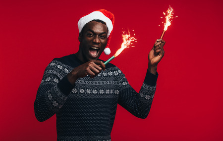 Excited young african man wearing santa hat celebrating with sparklers on red
