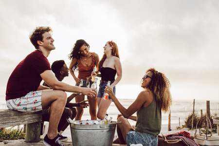Diverse group of friends hanging out by the beach with beers. Young people enjoying outdoors with beers. Imagens