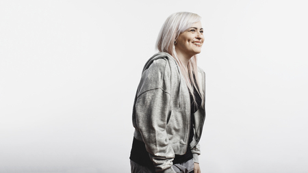 Happy woman with fashion piercing around her mouth and cheeks isolated on white background. Smiling fashionable woman in white hair looking away.