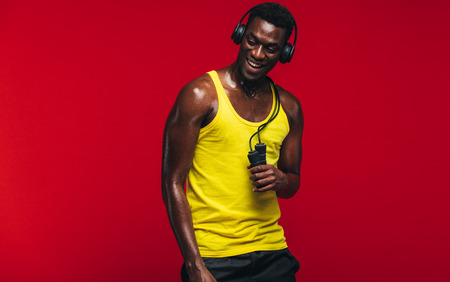 Fit young man listening to music on headphones with a skipping rope in hand on red