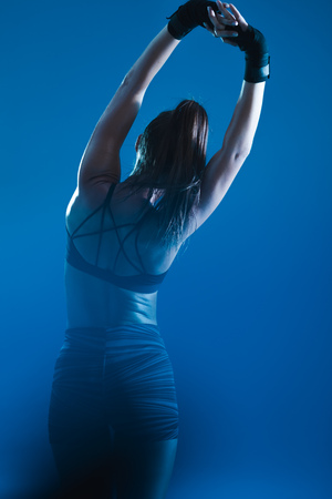 Rear view of woman in sportswear stretching against blue