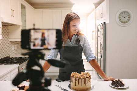 Smiling young woman standing at kitchen counter with pastries recording a content for her food blog channel. Imagens