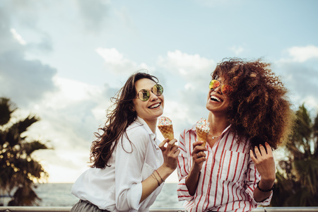 Two female friends enjoying ice cream together on a summer day. Cheerful young women eating icecream at seaside promenade.