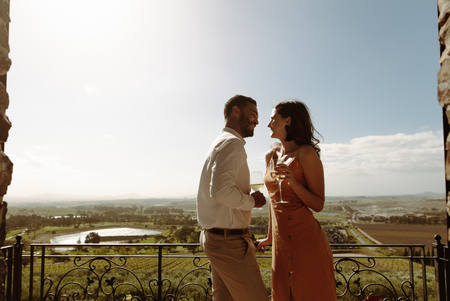 Romantic couple standing in the balcony of a farmhouse holding wine glasses
