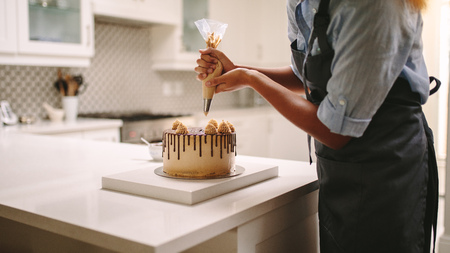 Female chef with pastry bag squeezing cream on cake at kitchen. Woman preparing a cake at home. Imagens