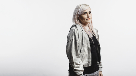 Woman with fashion piercing around her mouth and cheeks standing against white background. Fashionable woman with white hair and tattoo on body looking at camera.