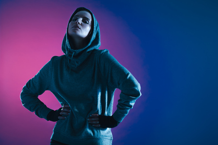 Sportswoman in hooded shirt looking at camera. Fitness woman posing against colored background.