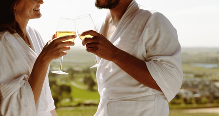 Close up of a couple toasting white wine. Cropped shot of a man and woman in bathrobe talking over a glass of wine.