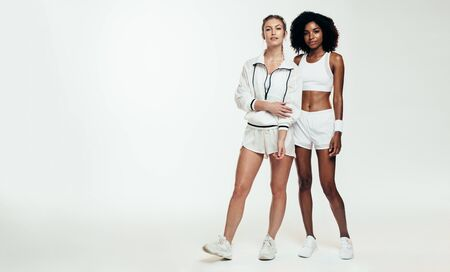 Full length of two women in sportswear standing over white background. Multi-ethnic sportswoman looking at camera.